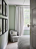 Gray upholstered armchair in corner of bedroom near window