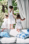 Three girls in white summer dresses climb around the window on a sofa