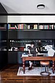 Frau sitzt am Holztisch vor schwarzer Schrankwand im Büro