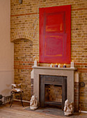 Red artwork above mantelpiece on brick wall