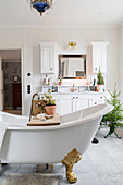 White, country-house-style bathroom with vintage-style free-standing bathtub