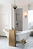 Free-standing bathtub with gilt claw feet and antique tap fittings