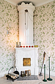 Antique, white stove in corner of living room with floral wallpaper