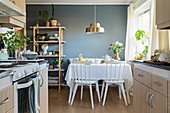 View from open-plan kitchen to set breakfast table in front of blue wall