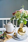 Flower in golden vase on set table