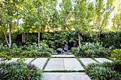 Weg aus großen Steinplatten durch sommerlichen Garten mit Skulptur