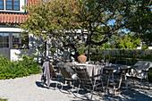 Set garden table on gravel terrace in summer garden