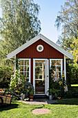 Falu-red, Scandinavian-style summerhouse in summer garden