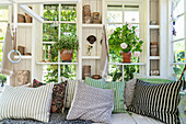 Scatter cushions with various patterns on bench in summerhouse