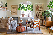 Pale grey sofa, leather pouffe, houseplants and anatomical illustrations in living room