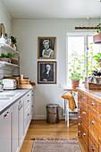 Kücheninsel aus alter Ladentheke in weißer Küche, schwarz-weiße Portraitfotografie an der Wand