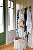 Wooden tub below coat rack in hallway