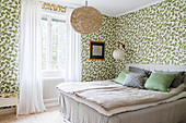 Double bed and leaf-patterned wallpaper in guest bedroom