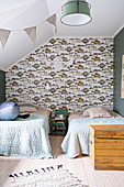 Twin beds and fish-patterned wallpaper in bedroom