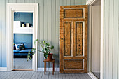 Rustic wooden door, houseplant on stool and view into living room