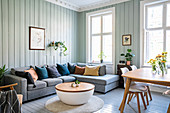 Grey sofa set, coffee table and dining area in living room with wooden walls painted pale green