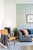 Retro armchair in front of fireplace and grey sofa set in living room with wooden walls painted pale green