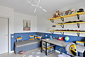 Shelves on wall, desk and bench in teenager's room with two-tone blue and white walls