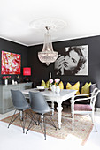 Chandelier and dark grey walls in eclectic dining area