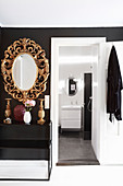 Opulent mirror with carved gilt frame next to bathroom door