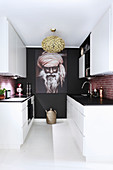 Large portrait on black end wall in white, modern kitchen
