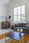 Coffee table, grey sofa, classic standard lamp and antique bureau in white-painted log cabin