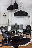 Two black, Baroque armchairs on cowhide rug below large ceiling lamps