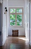 Wooden crate below window in sunny corridor with panelled walls