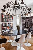 Deckenleuchte mit Gelenklampen überm Designertisch vorm Regal