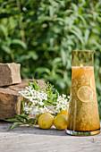 Fresh elderflower juice in a glass carafe decorated with elderflowers