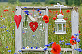 Heart-shaped decorations, cornflowers and candle lantern adorning window frame in poppy field