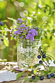 Late summer bouquet with Blue billygoat weed in glass jar with lace trim