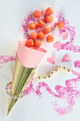 Sweets spilling out of paper cone next to string of lettered beads and love hearts