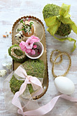 Moss eggs with ribbons and gold and pink Easter decorations