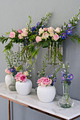 Roses and delphiniums in various vases