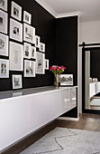 Gallery of pictures with white frames on black wall above sideboard