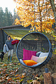 Colourful cushions in hanging chair in autumnal garden: woman in background carrying cushions and blanket