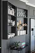 Crockery on grey wall-mounted shelves on grey wall above serving trolley