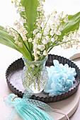 Strauß Maiglöckchen in einer Backform mit Papierblumen
