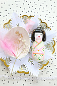 Geisha figurine on paper flower on plate with other decorations