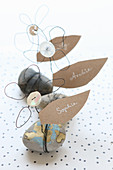 Name cards shaped like leaves on wire flowers on pebbles