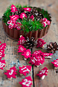 Numbered Christmas trees made from red felt and conifer twigs in flan tin