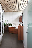Corner bathtub with wood panelling in bathroom