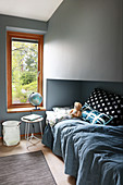 Blue bedspread and soft toy on bed next to globe lamp on windowsill in child's bedroom