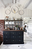 Black chest of drawers in rustic kitchen with chequered floor