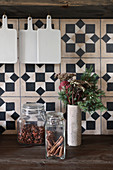 Storage jars and wintry vase of flowers against rustic tiles