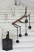 Black baubles, antlers and lantern on wall of log cabin