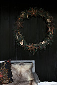 Fur blankets on garden bench and large wreath outside black wooden house