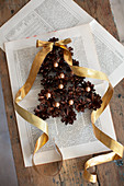 Christmas-tree shape made from pine cones and beads with gold ribbon on book pages