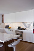 Elegant, white fitted kitchen with marble elements